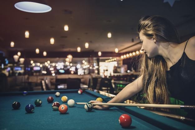 Bella mujer con pelo largo jugando al billar