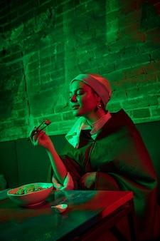 Bella mujer con un pendiente de perlas tomando el almuerzo en la cafetería moderna