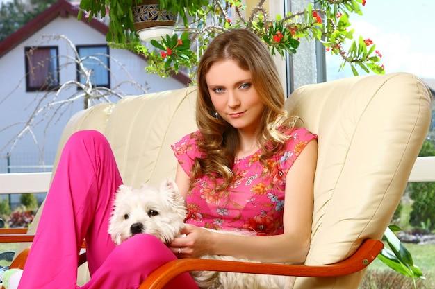 Bella mujer con perro blanco