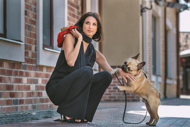 Bella mujer con perro en la calle
