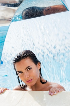 Bella mujer de pie en la piscina bajo la cascada y mirando al frente