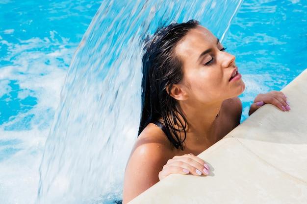 Bella mujer de pie en la piscina bajo la cascada