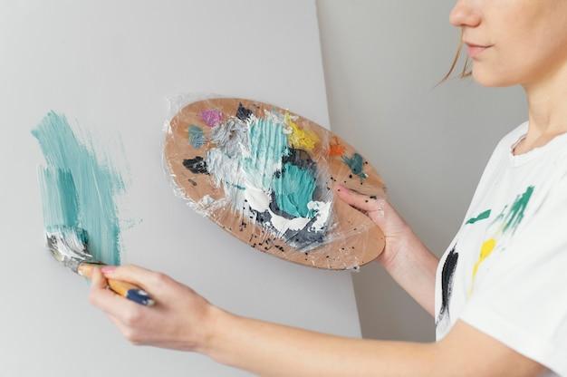 Bella mujer pintando con acrílicos sobre lienzo
