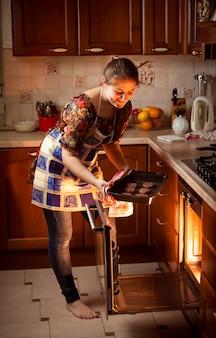 Bella mujer poniendo galletas de chocolate en el horno caliente