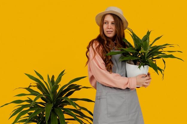 Bella mujer posando con macetas de plantas