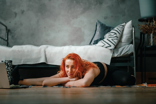 La bella mujer practica deportes en casa. alegre mujer deportiva con pelo rojo se extiende a la pierna y mira en la computadora portátil, blog de disparos en el dormitorio
