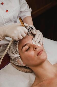 Bella mujer recibiendo un tratamiento cosmético en el centro de bienestar