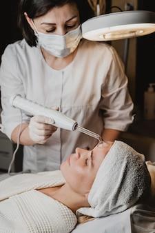 Bella mujer recibiendo un tratamiento facial en el centro de bienestar