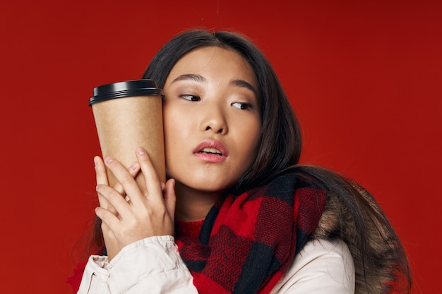 Bella mujer en un rojo abraza una taza de café