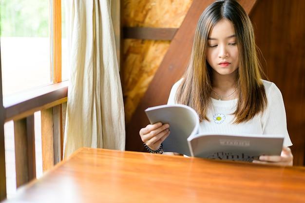 Bella mujer sentada en un café leyendo una revista