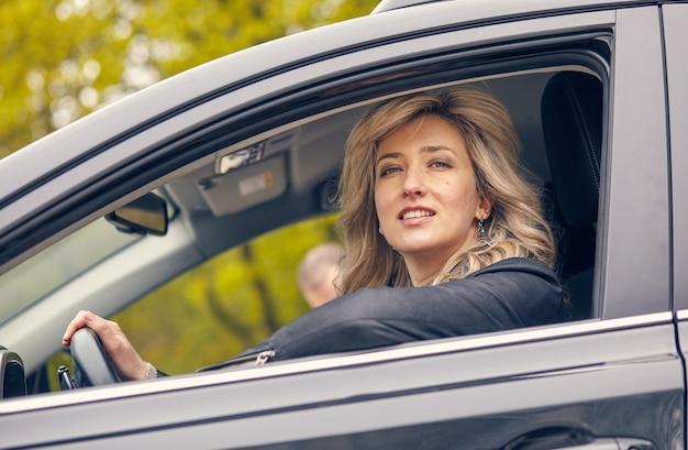 Bella mujer sonriente posando en la ventanilla del coche