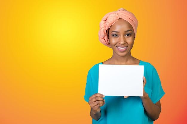 Una bella mujer con una sonrisa perfecta sostiene una tarjeta de visita
