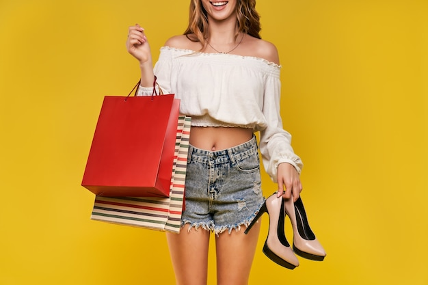 Bella mujer sosteniendo bolsas y zapatos en una pared amarilla