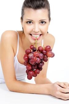 Bella mujer sosteniendo un racimo de uvas por sus dientes
