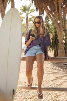 Bella mujer con tabla de surf en la playa