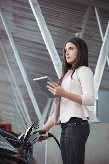 Bella mujer con tableta digital mientras carga el coche eléctrico
