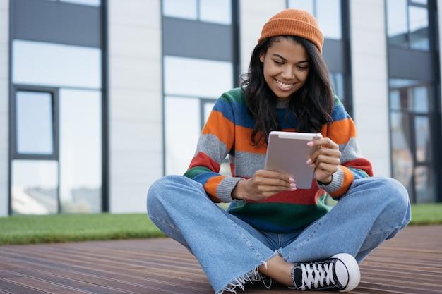 Bella mujer con tableta digital, viendo películas al aire libre