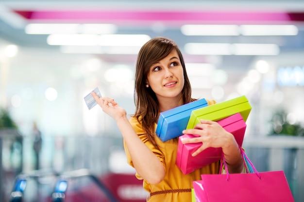 Bella mujer con tarjeta de crédito en el centro comercial