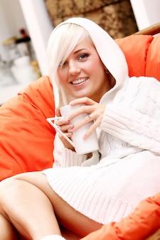 Bella mujer con taza de bebida caliente