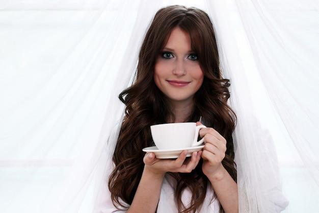 Bella mujer con taza de café caliente