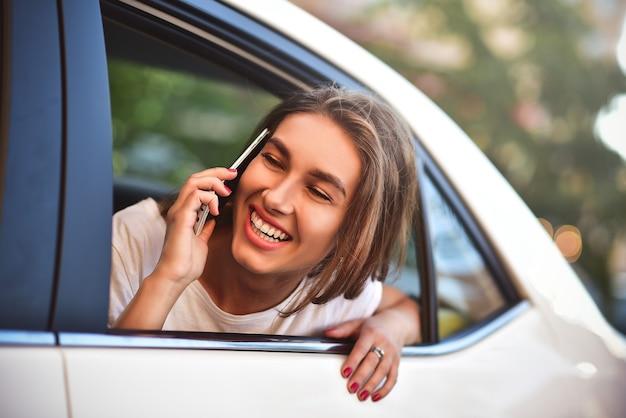 Bella mujer con teléfono sonriendo mientras está sentado en el asiento trasero del coche.
