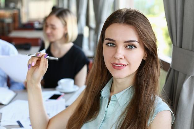 Bella mujer tiene reunión con sus subordinados en el café