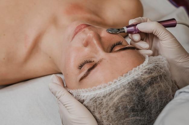 Bella mujer durante un tratamiento cosmético en el spa