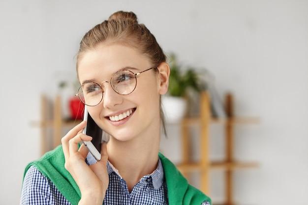 Bella mujer vestida formalmente en la oficina con teléfono