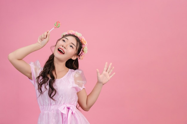 Una bella mujer vestida con una princesa rosa está jugando con su dulce caramelo en un rosa.