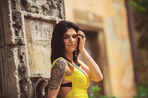 Una bella mujer con un vestido amarillo, tatuajes, posando para la arquitectura de fotos en lviv