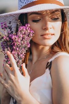 Bella mujer en vestido blanco en un campo de lavanda