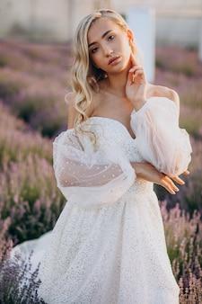 Bella mujer en vestido de novia en campo lavanda