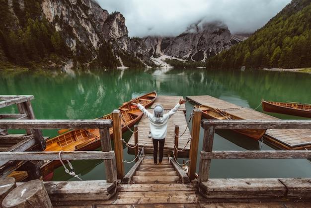 Bella mujer visitando un lago alpino en braies, italia