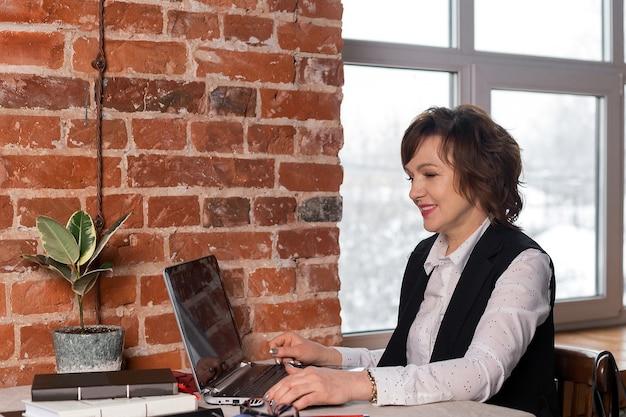 La bella, profesional y madura mujer trabaja en su computadora portátil. mujer de negocios.