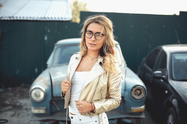 Una bella rubia con el pelo largo en pantalones cortos de mezclilla blanca se encuentra cerca de un viejo coche retro