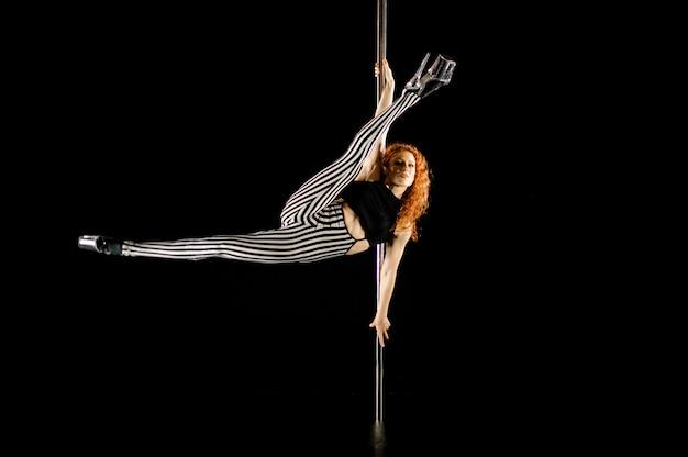 Bella y sexy mujer pelirroja realizando pole dance