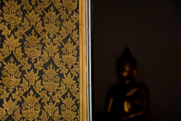 Bellas artes tailandesas tradicionales en una ventana en el antiguo templo