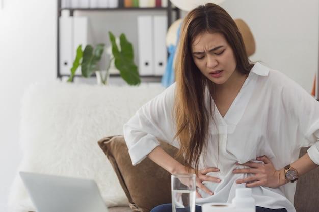 Las bellas mujeres asiáticas sienten cólicos menstruales y dolor de estómago después de la menstruación.