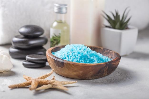 Belleza bodegón de aceite de masaje botella de aroma esencial y fragancia natural sal con piedras, velas en la mesa de hormigón gris. composición del tratamiento de spa.