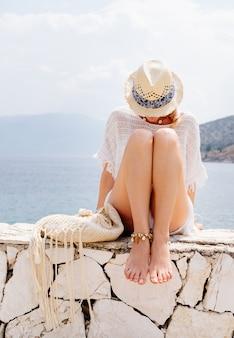 Belleza bronceada y elegante mujer joven con ropa blanca, sombrero de paja y gafas de sol sentado en la orilla del mar