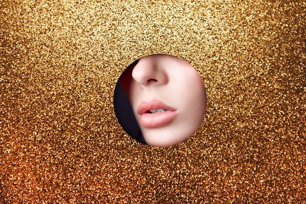 Belleza cara maquillaje labios regordetes chica en agujero redondo de papel de oro amarillo