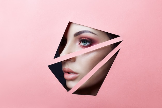 Belleza cara maquillaje rojo ojos joven en el agujero de papel rosa rosa.