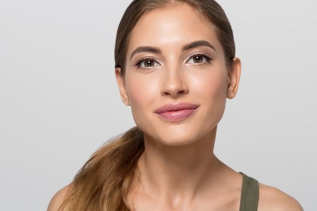 Belleza cara mujer sana piel limpia natural maquillaje concepto cosmético. fondo de color. gris