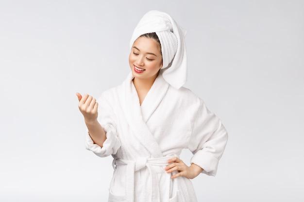 Belleza chica asiática que revisa su piel cuidado de la piel aislado sobre