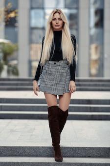 Belleza chica rubia caminando por la calle en ropa de estilo