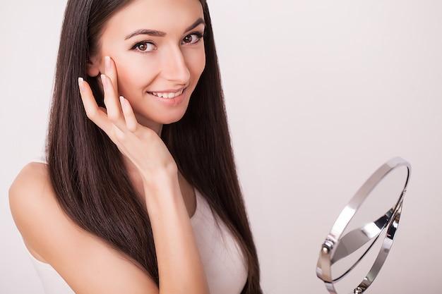 Belleza, cuidado de la piel y concepto de la gente: mujer joven sonriente que aplica la crema a la cara y mirando al espejo en el baño de su casa