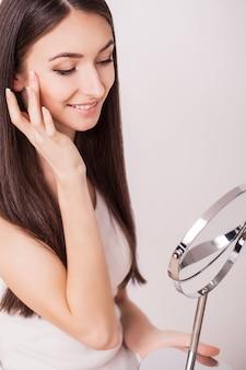 Belleza, cuidado de la piel y personas: sonriente mujer joven que aplica la crema para la cara y mirando al espejo en el baño de su casa
