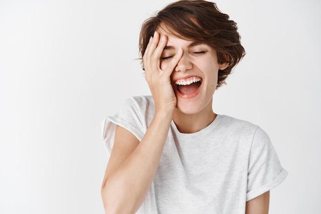 Belleza y cuidado de la piel. retrato de mujer caucásica feliz con pelo corto, tocando la piel facial suave y limpia y riendo sin preocupaciones, de pie con los ojos cerrados en la pared blanca