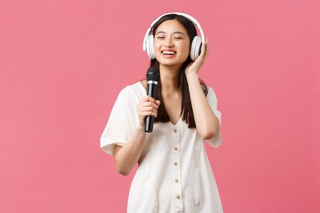 Belleza, emociones de las personas y concepto de tecnología. muchacha asiática feliz despreocupada que usa la aplicación del karaoke del teléfono móvil, cantando en el micrófono, escucha la música en los auriculares, fondo rosado.