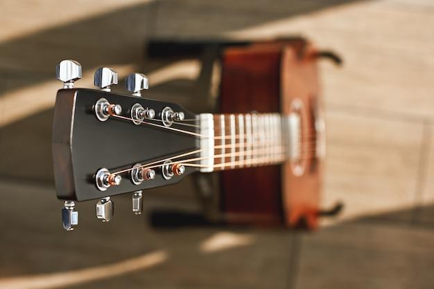 Belleza del instrumento musical. foto de vista superior creativa de la guitarra acústica marrón con foco en el cabezal contra el piso de madera. instrumentos musicales. concepto de música.